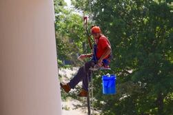 A man rappels against a building with full cleaning kit. He cleans windows and exterior surfaces.